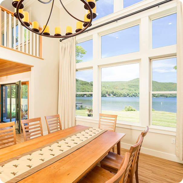 large wood dining table looking out windows over a lake